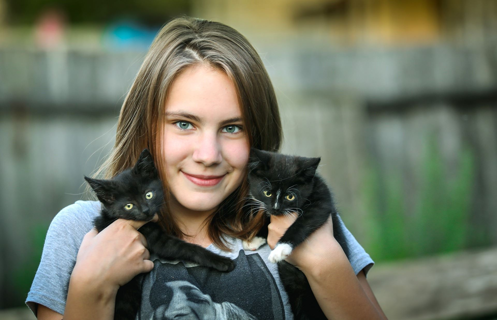 Girl holding two young black and white kittens--one in each arm